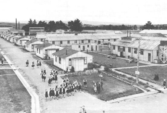 (24) The Pahiatua Camp contained dormitories, dining rooms, recreation hails, schools, a library, gymnasium, hospital, chapel and administrative building.  It had family cottages for the staff and tar-seated streets divided it into four sections.  The man in the centre of the picture is Mr S. Zaleski who became administrator of the camp after the first Delegate of the Polish Ministry of Education and Social welfare, Mr J. Sledzinski, was transferred in 1945.