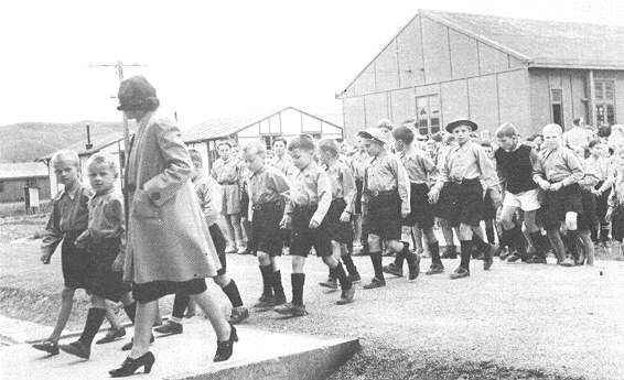 (27) On Sundays the children put an their best clothes and set out for the camp chapel that they had made in a large recreation hall of the Pahiatua complex.